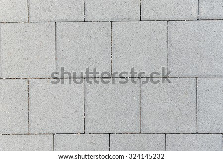 Concrete or cobble gray square pavement slabs or stones  for floor, wall or path. Traditional fence, court, backyard or road paving. - stock photo