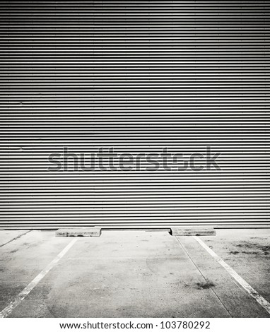 Concrete parking floor and tin wall. - stock photo
