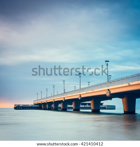 Concrete pier in Kolobrzeg, long exposure shot at sunset - stock photo