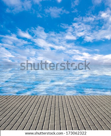 concrete pier on the sea and sky with clouds - stock photo