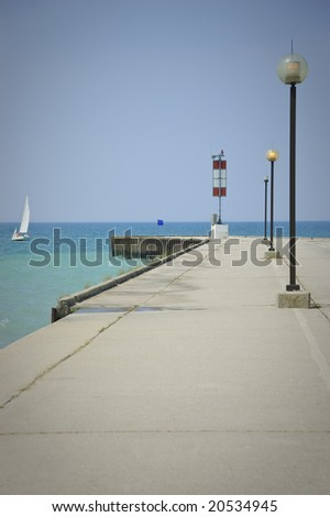 Concrete pier overlooking lake and sailboat under clear skies
