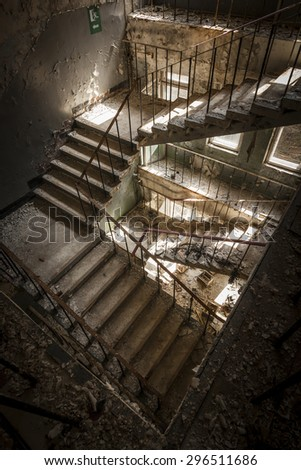Concrete stairs illuminated with a picturesque light in an abandoned building in a sunny day. The light enters through some windows