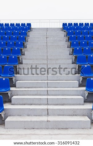 Concrete steps of pathway stairs on an university stadium with symmetrical placed blue seats on left and right sides of aisle. View from the bottom of stairs to top. Full length of pathway. No people - stock photo