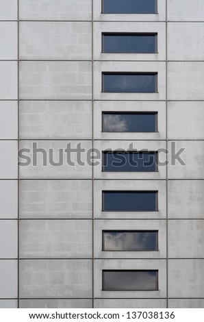 Concrete wall and windows with clouds reflection - stock photo