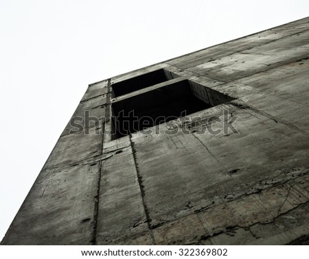 Concrete wall with window openings of the unfinished building against the white sky - stock photo