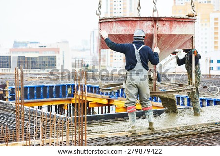 concreting work: construction site worker during concrete pouring into formwork at building area with skip - stock photo
