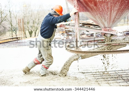 Concreting work. Construction site worker during concrete pouring into formwork at building area with barrel skip - stock photo