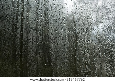 condensation droplets in a window glass, nature abstract background - stock photo