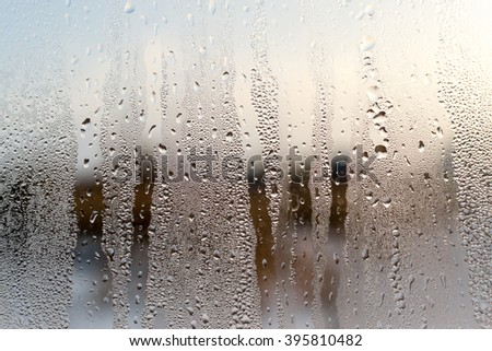 Condensation forms water droplets on the surface of a clear glass house interior window. Defocused background texture provides a brown colour. Copy space area for architecture domestic concepts - stock photo