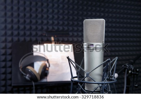 Condenser microphone in dark vocal recording room  - stock photo
