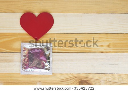 condom and red heart on wooden background. Dating,  Valentine's Day copy space concept. soft toned image - stock photo
