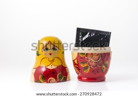 Condom in small pack placed inside single Russian wooden doll. A concept. - stock photo