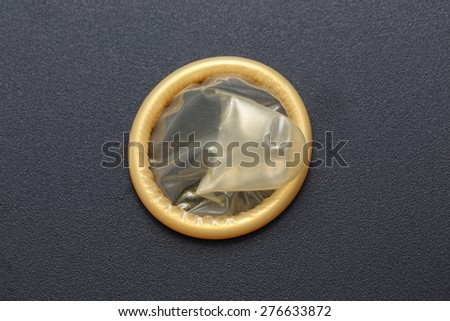 condom on black background - stock photo