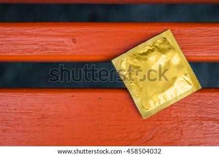Condom surface. Gold condom lying on the orange bench - stock photo