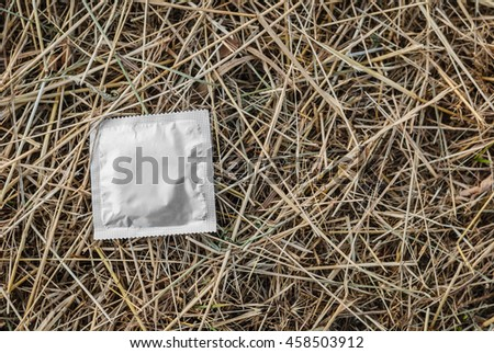 Condom surface. Silver condom lying in the manger - stock photo