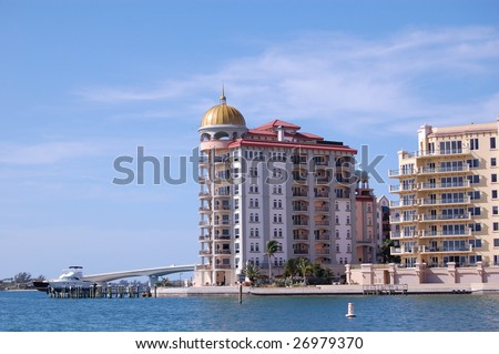 Condominium on sarasota bay in florida with the ringling bridge in the background and a yacht in front. - stock photo