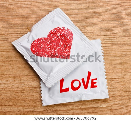 Condoms with heart on wooden table - stock photo