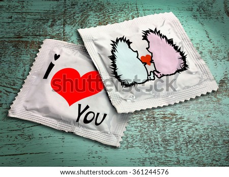 Condoms with pictures on wooden table - stock photo