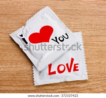 Condoms with text I love you on wooden table - stock photo