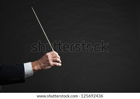 Conductor conducting an orchestra isolated.