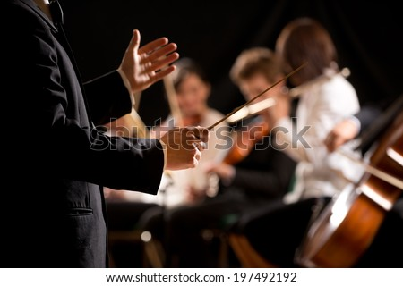 Conductor directing symphony orchestra with performers on background, hands close-up. - stock photo