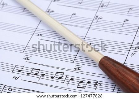 Conductor's baton and music score. - stock photo