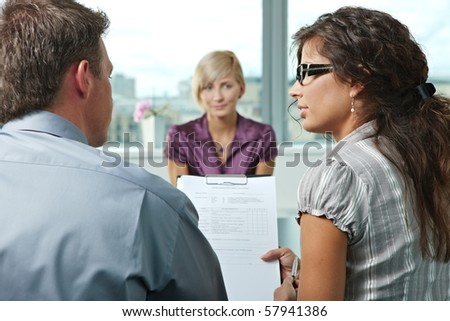 Conductors talking over the questionnaire form during the job interview. Over the shoulder view. Focus placed on people in foreground. - stock photo