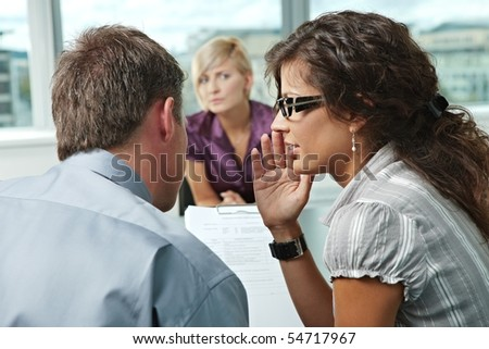 Conductors whispering over questionnaire form during the job interview. Over the shoulder view. Focus placed on people in foreground. - stock photo