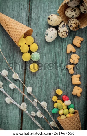 Cones are decorated for Easter quail eggs and candy colored jelly beans. Selective focus. - stock photo
