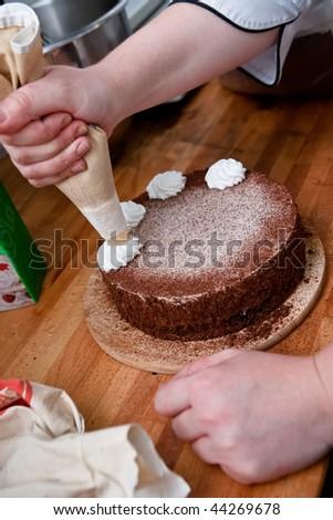 Confectioner is decorating chocolate cake - stock photo