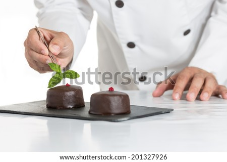 Confectioner putting the last ornament to a cake - stock photo