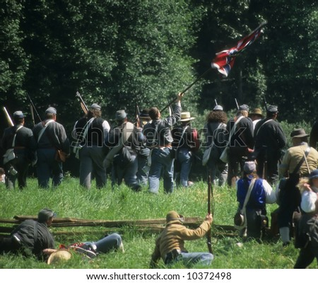 Confederate soldiers advance, Civil War battle reenactment - stock photo