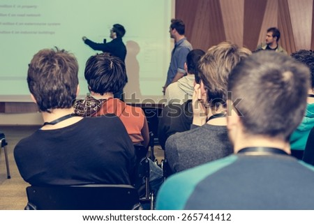 Conference hall with people listening to presentation. - stock photo