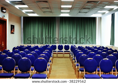 Conference hall with rows of blue chair - stock photo