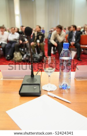 conference in hall. focus on bottle. much people in out of focus. - stock photo