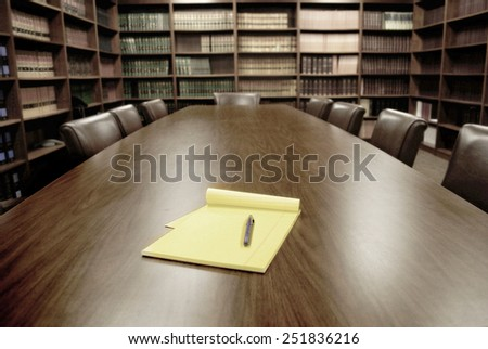 Conference room table with several leather chairs and shelves of books - stock photo