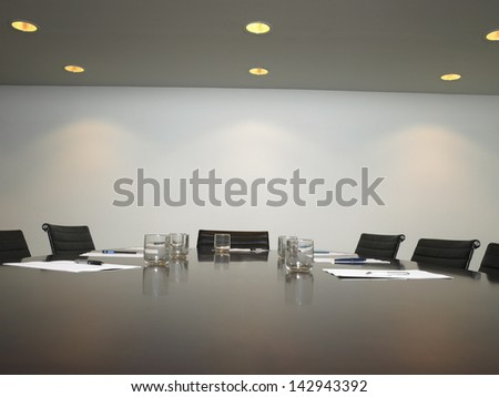 Conference room with arranged water glass and documents at table - stock photo