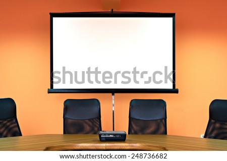 Conference room with empty chairs and a projector screen - stock photo