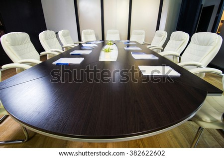 Conference round table and office chairs in meeting room - stock photo