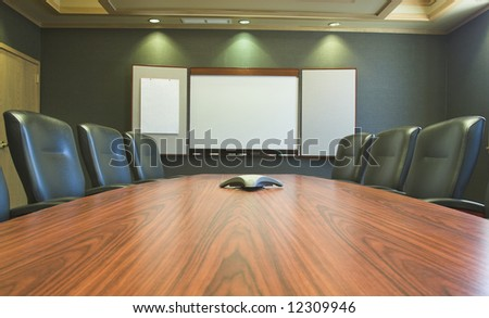 Conference table and blank presentation board. - stock photo
