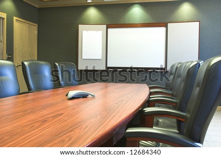 Conference table and blank presentation board - stock photo
