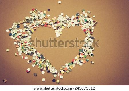 Confetti heart on a golden background / Confetti heart / Confetti heart on a golden background - stock photo
