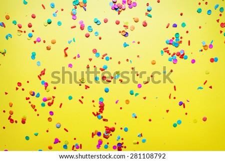 confetti on yellow background - stock photo