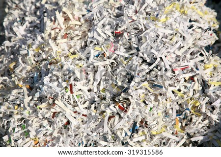 Confetti Shredded paper in a recycle trash can. The best way to keep safe from Identity Fraud is to confetti shred your important discarded documents. ID fraud is a rising form of theft world wide - stock photo