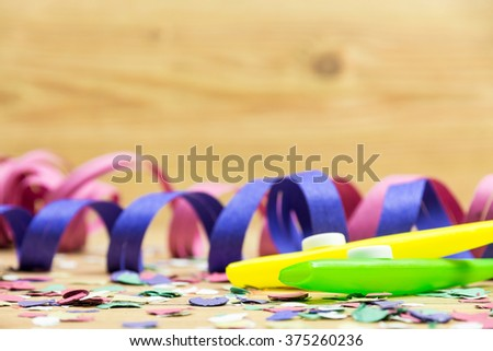 confetti, streamers and party whistle on wood background - stock photo