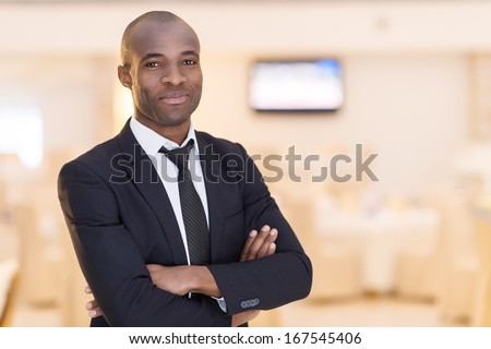 Confidence and charisma. Cheerful young African man in full suit keeping arms crossed and looking at camera - stock photo