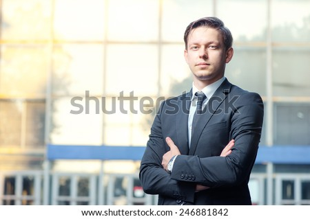 Confidence and charisma. Cheerful young businessman in full suit keeping arms crossed and looking at camera against office building - stock photo