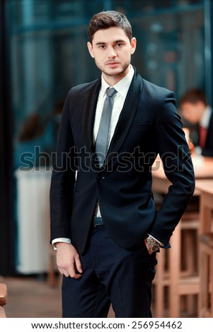 Confidence and charisma. Cheerful young businessman in full suit looking at camera while standing in the bar during business lunch - stock photo