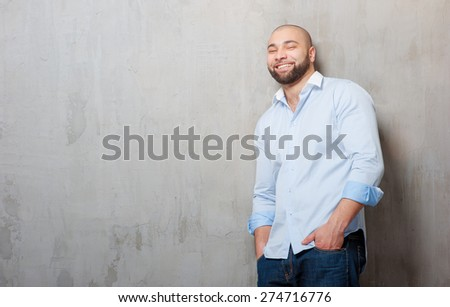 Confidence and charisma. Handsome young latin man holding hands in pockets and looking at camera while leaning on grey wall. - stock photo