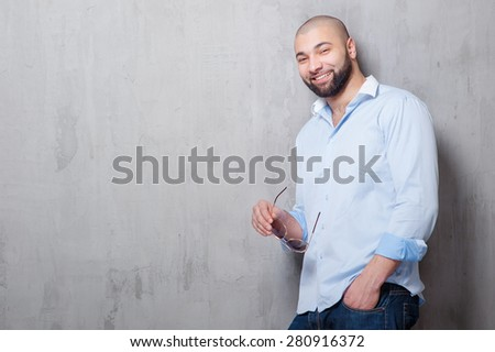 Confidence and charisma. Handsome young latin man holding sunglasses and looking at camera while leaning on grey wall. - stock photo
